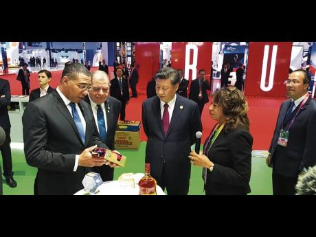 Jamaican Prime Minister Andrew Holness (left) shows off local products to Chinese President Xi Jinping (third left) while Agriculture Minister Audley Shaw and JAMPRO President Diane Edwards look on.