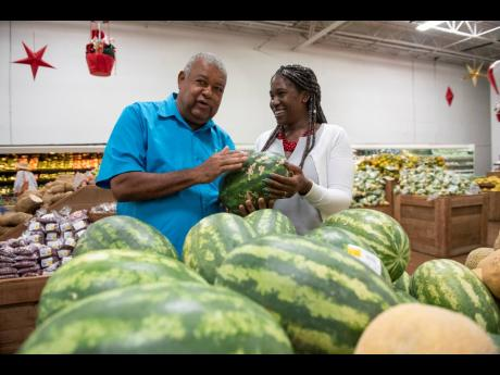 Lenworth Fulton (left), president of the Jamaica Agricultural Society, checks out locally produced watermelons with Monique Gibbs, chief technical director in the Ministry of Industry, Commerce, Agriculture and Fisheries, during the launch of Eat Jamaican Month at MegaMart in St Andrew on Friday.