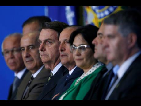 Brazil's President Jair Bolsonaro, centre, and his ministers attend the launch of the Green and Yellow programme to create formal jobs for young people, at the Planalto Presidential Palace, in Brasilia, Brazil, Monday, November 11, 2019.