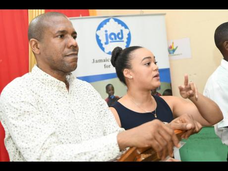 Kimberley Sherlock Marriott-Blake, executive director, Jamaica Association for the Deaf, addresses the association's annual general meeting at Lister Mair Gilby High School in Papine St Andrew, on Tuesday. Looking on is Christopher Williams, chairman.