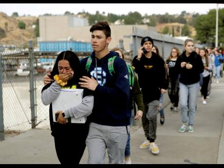 Students are escorted out of Saugus High School after reports of a shooting on Thursday, November 14, 2019, in Santa Clarita, Calif.