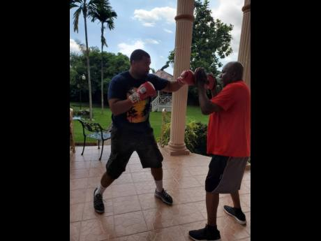 Former world heavyweight champion Mike 'The Bodysnatcher' McCallum (right) spars with his protege Christopher Lovejoy recently while back in his homeland Jamaica.