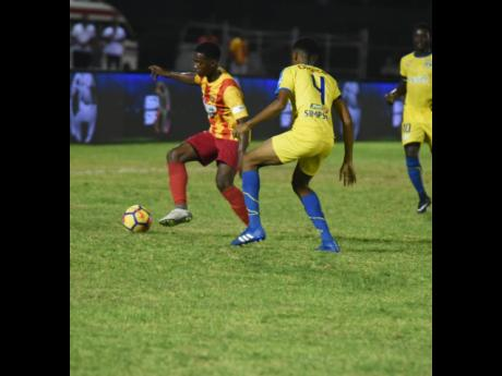Cornwall College's Solano Birch (left) attempts to dribble away from Clarendon College's Earl Simpson in the final of the ISSA/WATA daCosta Cup at the Montego Bay Sports Complex, on Saturday, December 1, 2018.
