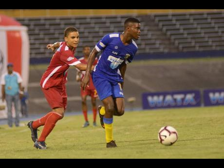 Shorn Hector/Photographer  Jamari Morrison (right) of Clarendon College eludes the challenge of Cornwall College defender Kamali Powell during their ISSA Champions Cup semi-final matchup at the National Stadium yesterday. Clarendon College won 3-0.