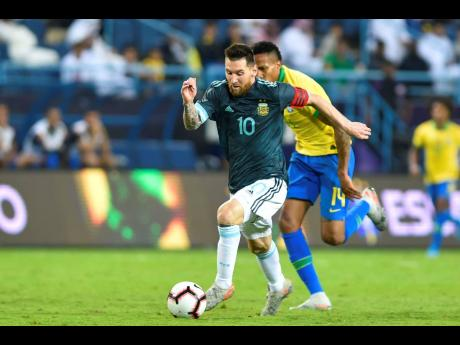 Argentina's Lionel Messi (front) dribbles by Brazil's Militao during a friendly international match at King Fahd Stadium in Riyadh, Saudi Arabia, on Friday.