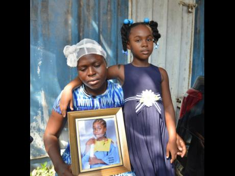 Japhene Campbell holds a picture of her seven-year-old son Benjamin Bair, who died in a freak accident at the Clan Clarty Primary School last month, with her daughter, eight-year-old Seraphine Bair, as they attended church on the weekend.