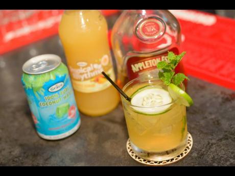 Grace Tropical Rhythms fruit drink sits next to a bottle of Appleton rum.