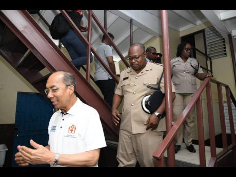Dr Horace Chang (left), minister of national security, tours the newly renovated Trench Town Police Station in Kingston yesterday. Following behind him are Superintendent Howard Chambers and Inspector Grace Gordon.
