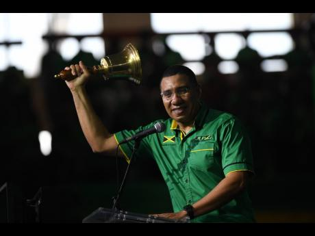 JLP President Andrew Holness rings the bell as his final act following his presentation at the National Arena on Sunday.