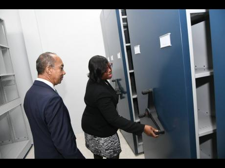Judith Mowatt, executive director of the Institute of Forensic Science and Legal Medicine, gives Dr Horace Chang, minister of national security, a tour of the Hope Boulevard, St Andrew, facility on Wednesday.