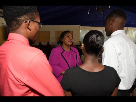 Rosalee Gage-Grey (second left), CEO of the Child Protection and Family Services Agency, gives a word of encouragement to wards of the State who did well in their CSEC and CAPE examinations for 2019. They were attending the CPFSA 2019 Educational Achievement Awards Ceremony at the Terra Nova Hotel on Thursday.