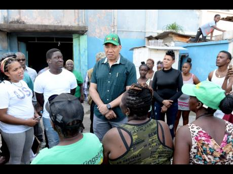 Prime Minister Andrew Holness (centre) speaks to residents in Rasta City, located in Tivoli Gardens, following a tour of the area on Saturday, November 30.