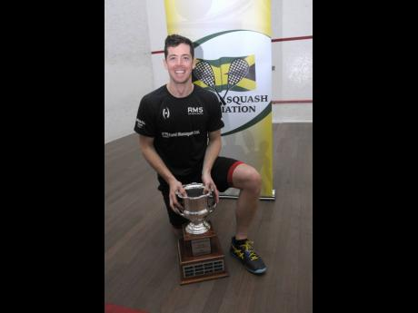 Chris Binnie holds the All-Jamaica Men's Senior Squash Champion trophy after winning it for the ninth time at this year's event at the Liguanea Club in New Kingston on the weekend.