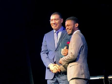 Sujae Boswell (right) receives the Prime Minister's Youth Award from Andrew Holness.