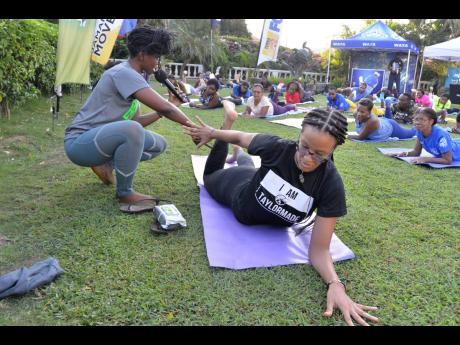 Yoga instructor Jo-Hanna Taylor (left) explaining the correct form for a yoga pose.