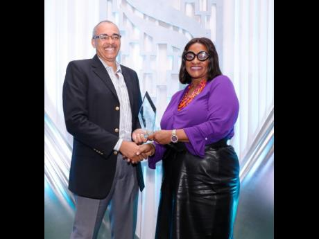 Jacqueline Brown-Barnes, assistant vice-president, group insurance services, employee benefits division, Sagicor Life Jamaica, presents an award to Dr Steve Mullings, one of 10 medical practitioners to receive recognition awards from Sagicor Life for excellence in service delivery, during an awards ceremony at the Golf View Hotel in Mandeville.