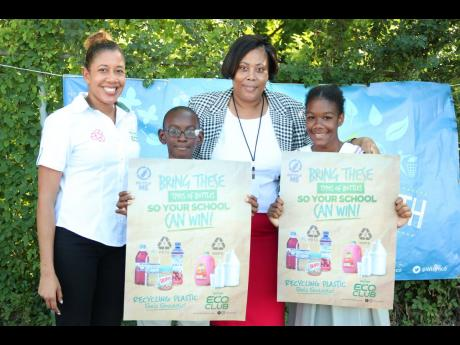 Wisynco ECO's marketing assistant, Christine Rankine (left), and Horizon Park Primary and Infant School's Principal, Shernette King-Nicholas, join grade-six prefects Dante Allen (second left) and Coleen Hart (right) as they show off posters displaying images of plastic bottles eligible for recycling. On  November 4, Wisynco ECO Troopers (staff volunteers) on-boarded the school as part of their mission to sensitise Jamaicans about recycling.