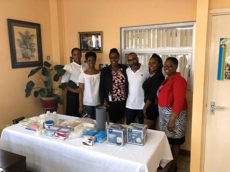 Martin Greaves (centre) with Mandeville Hospital staff during a handover of several medical instruments.