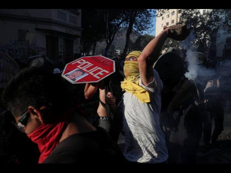 Anti-government protesters clash with police in Santiago, Chile, on Monday, November 18. Chileans have been demonstrations over inequality and better social services.
