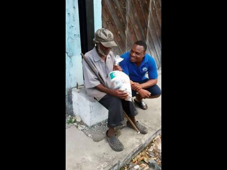 Ricardo Burke of the Yutes4Change charity group gifts toiletries to an elderly resident.