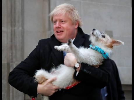 Britain's Prime Minister and Conservative Party leader Boris Johnson holds his dog, Dilyn, as he leaves after voting in the general election at Methodist Central Hall, Westminster, London, yesterday.