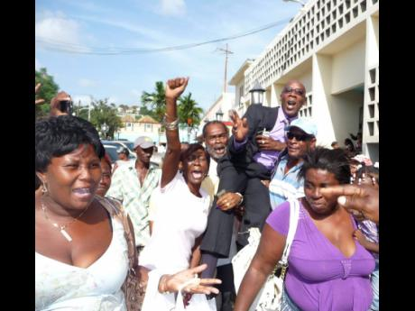 Supporters hoist Councillor Michael Troupe after he was freed of gun and ammunition charges.