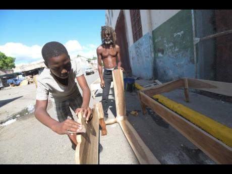Lanzel McCarthy III sanding down a bed frame yesterday under the supervision of his grandfather, Lanzel McCarthy I, at their woodwork operation along Matthews Lane in downtown Kingston.