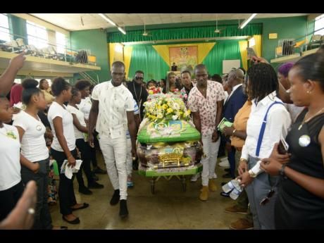 Pall-bearers pull the coffin of late national senior women's football team player Tarania 'Plum Plum' Clarke as family and friends look on at her funeral , held at the Excelsior High School Auditorium in Kingston yesterday.