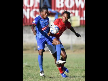 Dunbeholden's Nickoy Christian (left) and Thorn Simpson of UWI FC  battle for possession during last Sunday's Red Stripe Premier League match at the UWI Bowl. The game ended 0-0.