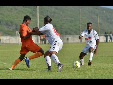 UWI FC player Fabian McCarthy (right) hurries to the scene as teammate Damano Solomon (centre) tussles with Tivoli Gardens' Stephen Barnett during their Red Stripe Premier League encounter at the UWI Mona Bowl on Sunday, September 1, 2019.