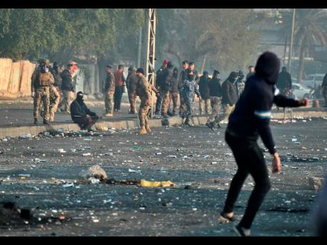 An anti-government protester throws a stone towards security forces during an ongoing protest in central Baghdad, Iraq on Monday.
