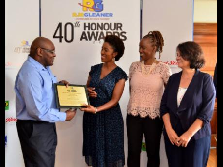 General manager of The Gleaner Company, Garfield Grandison, presents a Special Award to co-founders of Kingston Creative, Andrea Dempster-Chung (second left), and Dr Jennifer Bailey (second right), as well as Doris Gross, director, yesterday.