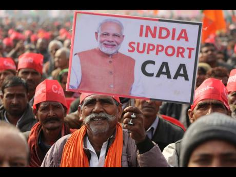 A supporter of India's Bharatiya Janata party holds a banner in support of new citizenship law with the photograph of Indian Prime Minister Narendra Modi during a rally in Lucknow, India, Tuesday, January 21, 2020.