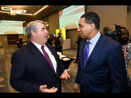Prime Minister Andrew Holness (right) has a convo with Stephen Beatty of KPMG Canada at the Caribbean Infrastructure Finance Forum 2020 at the AC Marriott Hotel in New Kingston on Tuesday.