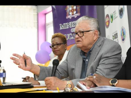 Chief inspector of the National Education Inspectorate, Maureen Dwyer, looks on as stand-in minister with responsibility for education, Karl Samuda, responds to questions from journalists at a briefing on the findings of the NEI report at Pembroke Hall High School on Friday.