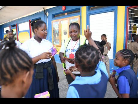 Jennifer Josephs, a temporary vector-control worker, handing out pamphlets to students of Friendship Primary School during a dengue clean-up exercise at the St Catherine school yesterday.