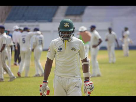 Jamaica Scorpions batsman Marquino Mindley leaves the field after he was dismissed by Barbados Pride fast bowler Chemar Holder.