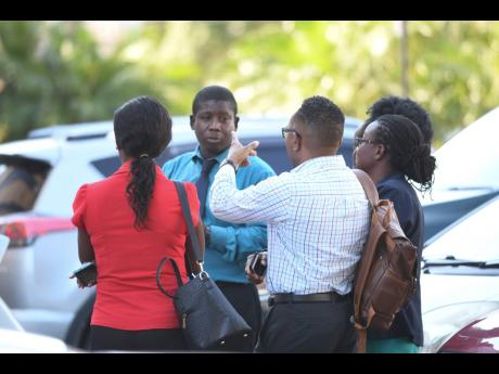 Staff of the Ministry of Education gather outside the multistorey Heroes Circle headquarters moments after a magnitude-7.7 earthquake shook Jamaica and several countries in the Americas.