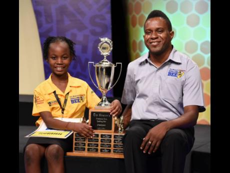 Toriann Beckford, The Gleaner's Children's Own Spelling Bee champion for 2020, poses with coach Errol Campbell shortly after acing the championship word U-V-A-R-O-V-I-T-E yesterday.