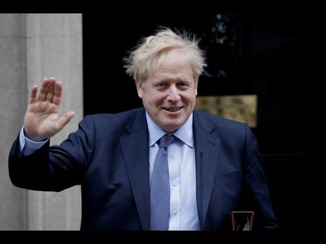 British Prime Minister Boris Johnson waves at the media as he leaves 10 Downing Street in London, to attend the weekly Prime Minister's Questions at the Houses of Parliament, in London, Wednesday, Feb. 5, 2020. (AP Photo/Matt Dunham)