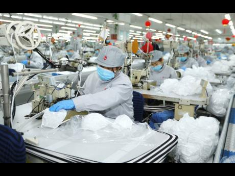 In this photo released by Xinhua News Agency, workers produce face masks in the workshop of a textile company in Jimo District of Qingdao in eastern China's Shandong province on Wednesday, February 12.