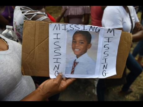 A resident holds a photo of Mark Leslie, the 11-year-old Mannings Hill Primary student who was found dead in Temple Hall.