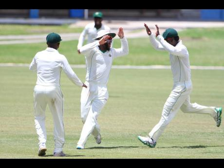 Jamaica Scorpions players Andre McCarthy (left), John Campbell (centre), and Paul Palmer Jr celebrate a wicket during a recent CWI Professional Cricket League Regional Four-Day Championship match at Sabina Park in Kingston.