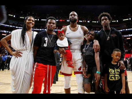 Dwyane Wade poses for a photo with his wife, Gabrielle Union, nephew, Dahveon Morris, and children, Kaavia James Union Wade, Zion (Zaya) Wade, Zaire Wade, and Xavier Wade.