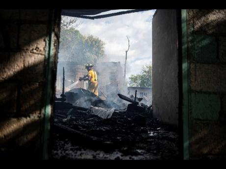 Firefighters extinguish a fire that destroyed three homes in 'Vietnam', a community located off Grants Pen Drive in St Anrdew, on Wednesday. Seven people are now homeless.
