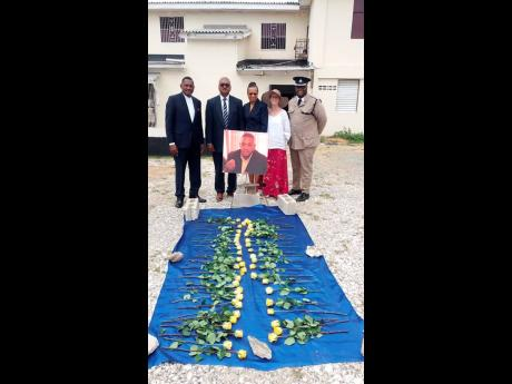 (From left) Bishop Everton Thomas, Dr Donovan Thomas, Faith Thomas, Meta Dunn, and Pastor Dr Kevin White, Jamaica Constabulary Force Area Four deputy chaplain, pose behind a floral tribute for slain businessman Wayne Stanbury, at the Emmanuel Apostolic Church on Slipe Road in Kingston yesterday. Photo by Jason Cross