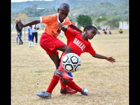 Benders Football Club's Nicholas Ayre (left) rides a tackle from Malik Campbell of Ballaz Academy during their Under-9 match at the Victory Cup youth football tournament at G.C Foster College on Saturday. Bender won the match 1-0.