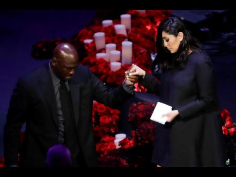 Vanessa Bryant (right) is helped off the stage by former NBA player Michael Jordan after speaking during a celebration of life for her husband, Kobe Bryant, and daughter Gianna yesterday in Los Angeles.