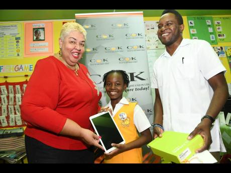 Ambassador Aloun Assamba, CEO, COK Sodality, presents a tablet to National Spelling Bee Champion Tori-Ann Beckford from McAuley Primary School in Spanish Town, St Catherine, and a gift to her coach, Errol Campbell, at the school recently.
