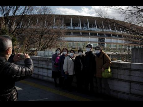 Tourists wear masks as a precaution for the coronavirus as they pause for photos with the New National Stadium, a venue for the opening and closing ceremonies at the Tokyo 2020 Olympic in Japan on Sunday.